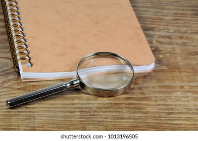 Magnifying glass with blank closed notebook on wooden background.