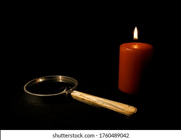 A magnifying glass and candle against a dark background.