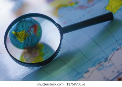 Magnifying glass close up with colorful map and globe.