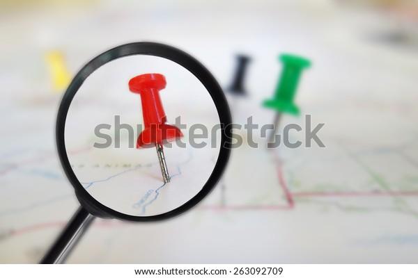 Magnifying glass closeup of push pin tacks in a map