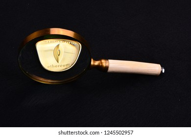 A magnifying glass distorting a bit coin by the angle of view making the round coin appear trapezoidal.