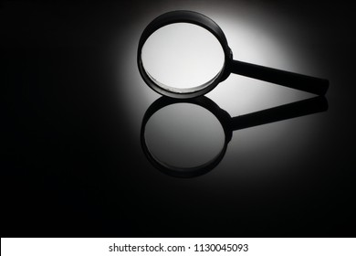 Magnifying glass with dramatic light on shiny, reflective black background for mirror effect.