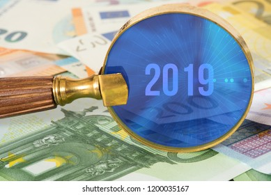 A magnifying glass, euro bills and the year 2019