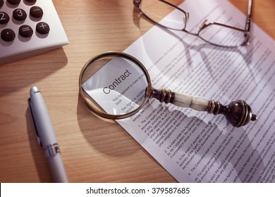 Magnifying glass examining and signing a legal contract document