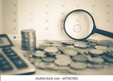 magnifying glass focus on deadline calendar with some coin and calculator in foreground, overdue, reminder concept