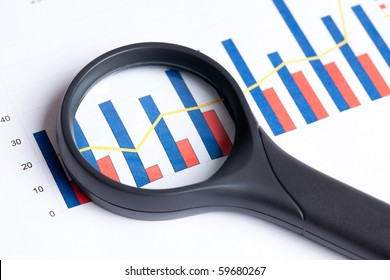 the magnifying glass focusing on business graph
