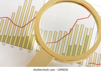 A magnifying glass focusing on a positive earning chart.