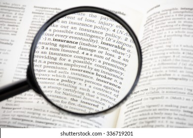 Magnifying glass focussed on the word 'insurance' on the page of a generic dictionary.