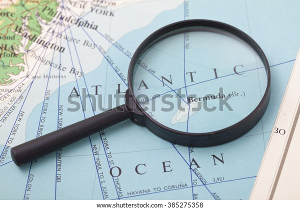 Magnifying Glass in front of a Bermuda map