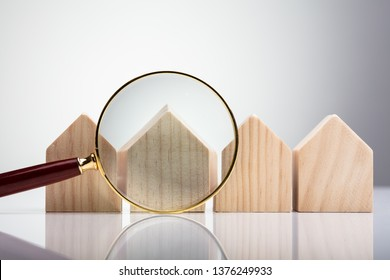 Magnifying Glass In Front Of Wooden House Model Arranged In A Row