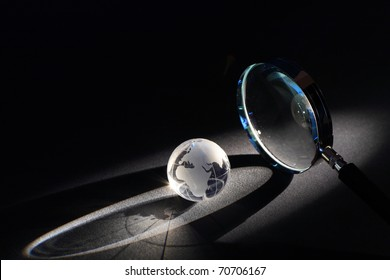 Magnifying glass and globe on dark background with beam of light