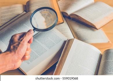 magnifying glass in hand and book on the table