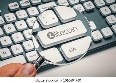 magnifying glass in hand focused on computer key with litecoin logo. cryptocurrency trading and mining concept