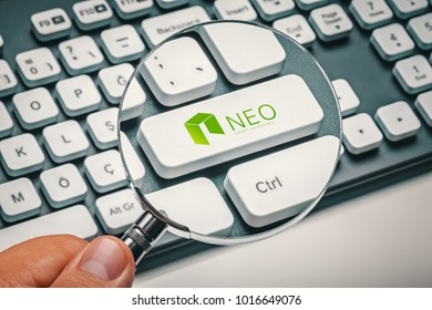 magnifying glass in hand focused on computer key with neo coin logo. cryptocurrency concept
