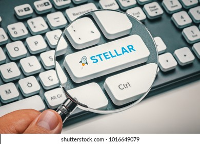 magnifying glass in hand focused on computer key with stellar logo. cryptocurrency trading concept