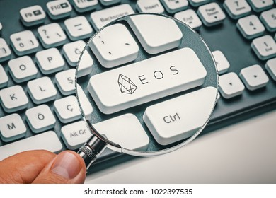 magnifying glass in hand focused on computer key with eos coin logo. cryptocurrency concept