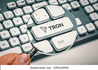 magnifying glass in hand focused on computer key with tron coin logo. cryptocurrency concept trading concept