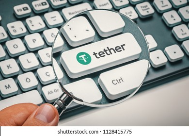 magnifying glass in hand focused on computer key with tether coin logo. cryptocurrency concept
