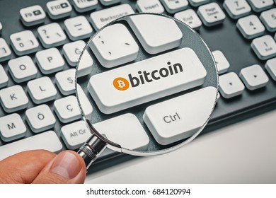 magnifying glass in hand focused on computer key with bitcoin logo