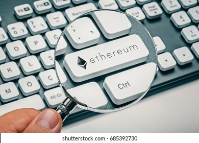 magnifying glass in hand focused on computer key with ethereum logo