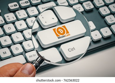magnifying glass in hand focused on computer key with bitcoin cash logo