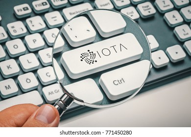 magnifying glass in hand focused on computer key with iota coin logo. cryptocurrency concept
