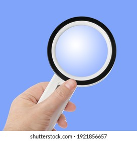 Magnifying glass in hand isolated on blue background