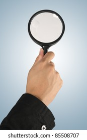 Magnifying glass in hand  on blue background  (path in side)