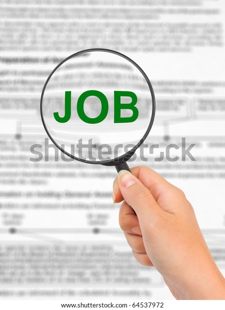 Magnifying glass in hand and word Job - business concept