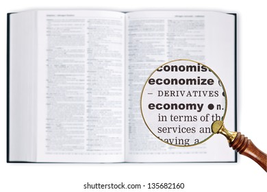 A magnifying glass held over a dictionary looking at the word ECONOMY enlarged