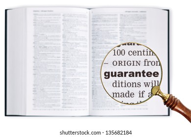A magnifying glass held over a dictionary looking at the word Guarantee enlarged
