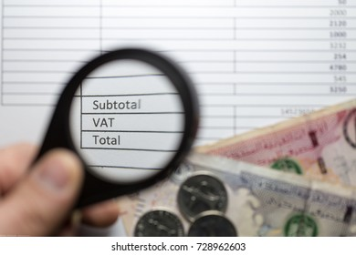 Magnifying glass hold over VAT word. UAE dirhams banknotes and coins on a invoice with VAT box. UAE will implement VAT at the rate of 5% on 1 January 2018.