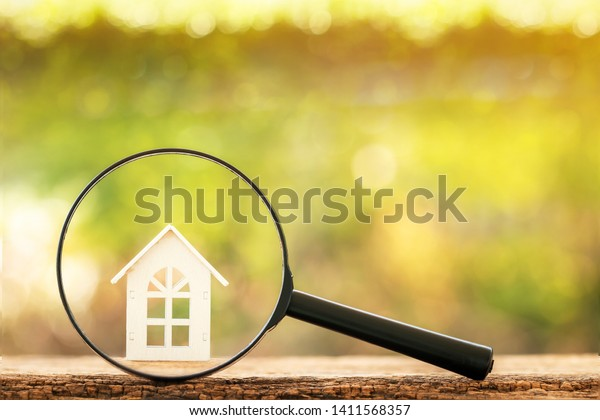Magnifying glass with home model put on the wood on bokeh background, Loan for real estate and searching for buy a new house to family in the future concept.