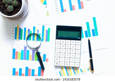 The magnifying glass lies on papers with color charts, pen and calculator on white background. Analyzing finances. Graph. Top view. Business concept.