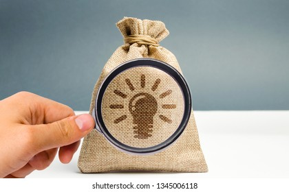 A magnifying glass is looking at a bag with a light bulb image of ideas and inspiration. Generation of innovative business ideas. Creative process. The accumulation of experience and skills.
