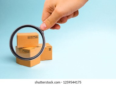 Magnifying glass is looking at the bunch of boxes on a blue background. The concept of moving to a new home, delivery of goods or commerce. Production, industry and warehousing of goods. import