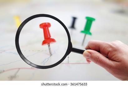 Magnifying glass looking at closeup of push pin tacks in a map
