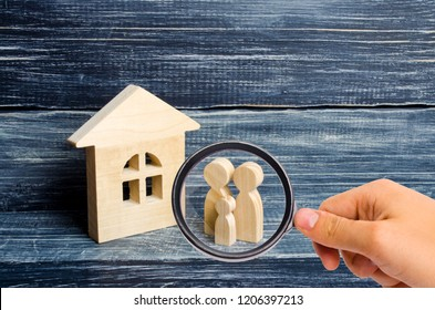 Magnifying glass is looking at the Family is standing near the house. Wooden figures of persons stand near a wooden house. The concept of a couple in love, cohabitants, parents, buyers