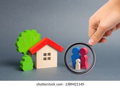 Magnifying glass is looking at figures of the family and house on an gray background. real estate, your own home. Affordable housing on credit or mortgage. Renovation and construction. Subsidies
