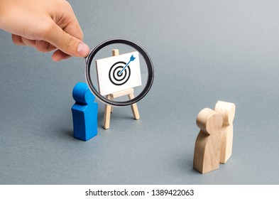 Magnifying glass is looking at leader explains employee tactics of advertising targeting. Training, briefing. Search strategies for effective advertising campaigns, customer reach. Business processes