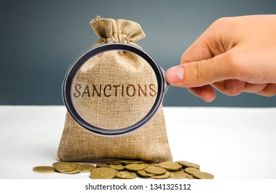 A magnifying glass is looking at a money bag with the word Sanctions. The imposition of economic and political sanctions on the subjects of geopolitics. Restriction and pressure of the world community
