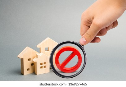 Magnifying glass is looking at the No Sign and the wooden house. Unavailability of housing, busy or low supply. Inaccessible and expensive housing. Seizure and freezing of assets. Selective focus