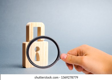 Magnifying glass is looking at the padlock on a gray background. information safty. concept of the preservation of secrets, information and values. Protection of data and information. Selective focus