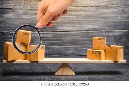 Magnifying glass is looking at the piles of boxes on the scales. Trade balance and calculation by barter. import and export of goods. Trade balance. Goods turnover between two subjects or countries.