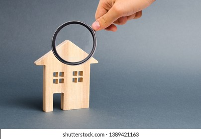Magnifying glass is looking at a wooden residential house on a gray background. Mortgage and credit for the purchase. Real estate concept, buying affordable housing, real estate renting. Property tax.