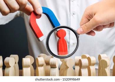 A magnifying glass looks at a red figure of a man from the crowd pulled by a magnet. leader manages the business and forms a team. toxic, incompetent worker. Increase team efficiency, productivity.