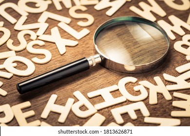 Magnifying glass with many wood letters of English alphabets, searching words to communicate, learning English concept