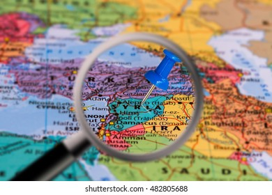 Magnifying glass with the Map of Syria with a blue pushpin stuck