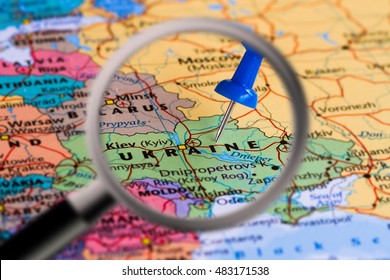 Magnifying glass with the Map of Ukraine with a blue pushpin stuckMap of Ukraine with a blue pushpin stuck