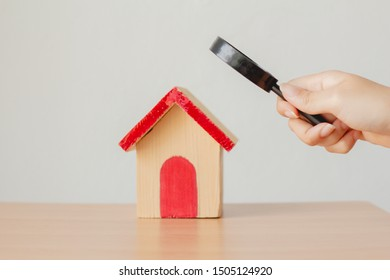 Magnifying glass with mini wood house model on green background, Home inspection concept.